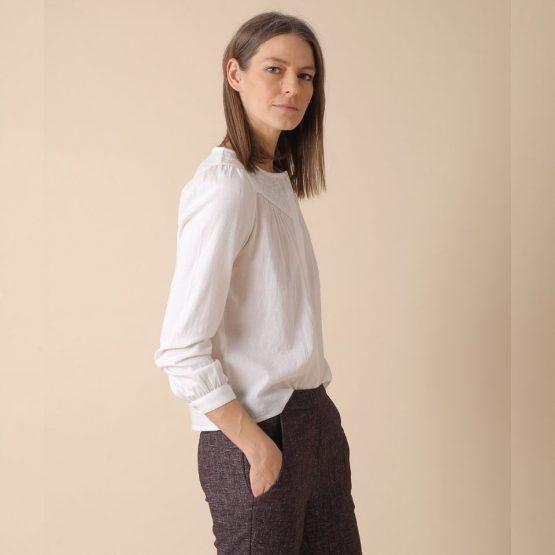 Blusa blanca de manga larga con cuello redondo y bordados en el canesú