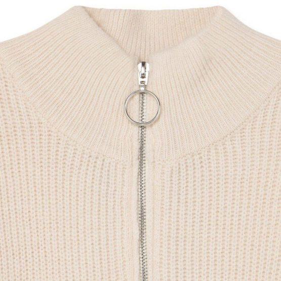 Jersey grueso con cremallera en el cuello y de color crudo con rayas finas en el cuerpo.